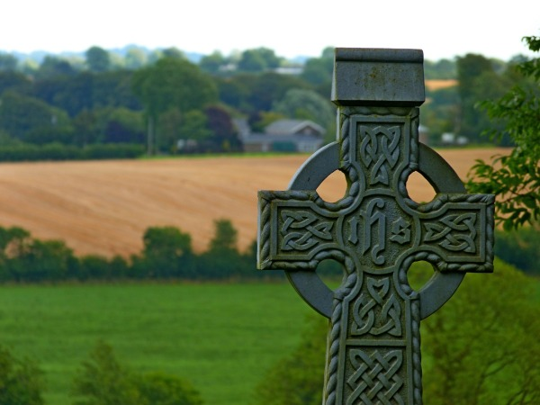 Celtic cross with fields behind it